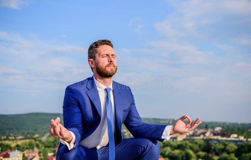 Il vestito convenzionale dell'uomo d'affari si siede la posa del loto e meditare all'aperto Prova dell'uomo per tenere il suo men immagine stock libera da diritti