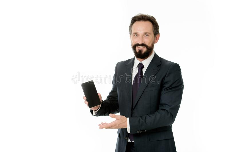 Il vestito convenzionale dell'uomo d'affari tiene lo smartphone L'uomo d'affari barbuto dell'uomo felice annuncia l'applicazione  fotografia stock libera da diritti