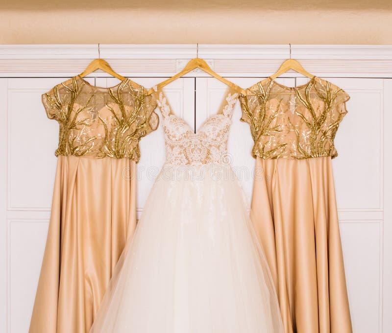 Il vestito da sposa splendido e gli abiti beige per le damigelle d'onore appendono più fotografie stock