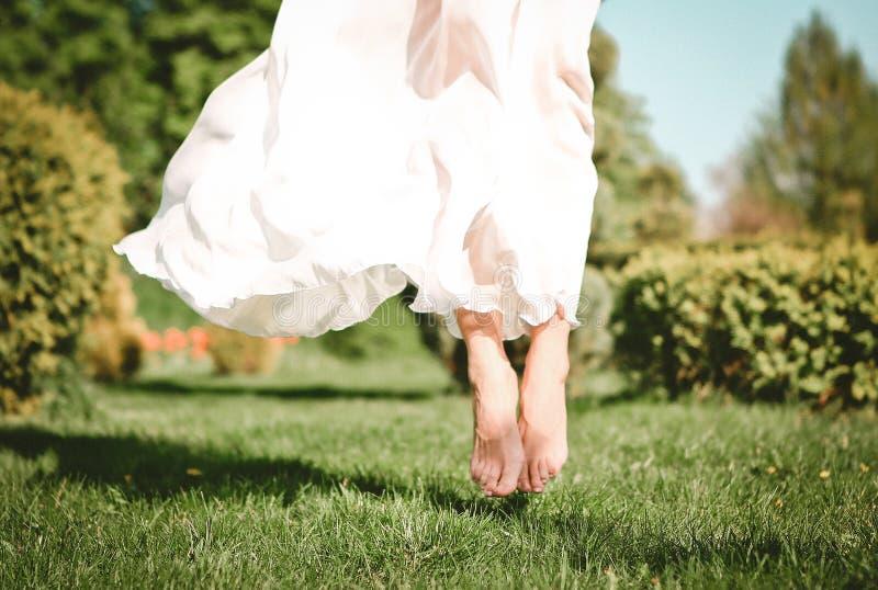 Il vestito dall'esterno della ragazza ha saltato a piedi nudi l'erba immagine stock
