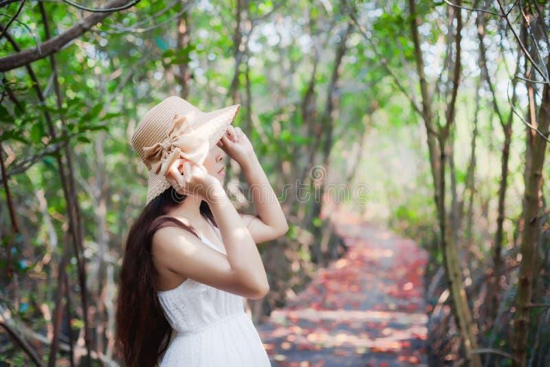 Il vestito dalla bella donna asiatica ed il cappello di paglia bianchi d'uso godono della vista con un sorriso , Stando su un pon fotografia stock libera da diritti