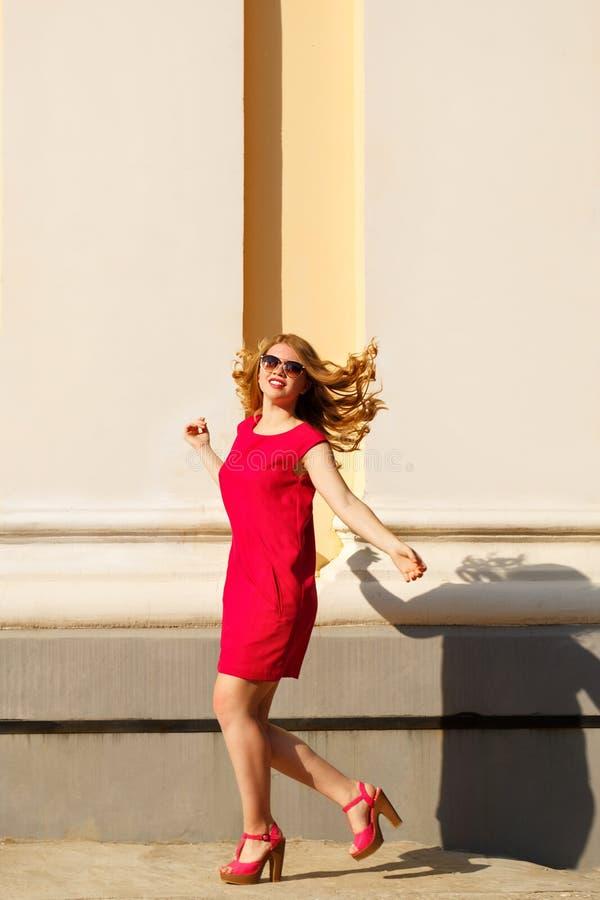 Il vestito dalla ragazza in rosso, gli occhiali da sole ed i capelli ricci immagini stock libere da diritti