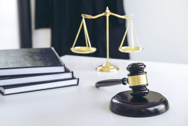 Il vestito dell'avvocato, libri di legge, un martelletto e bilancia della giustizia su w fotografia stock