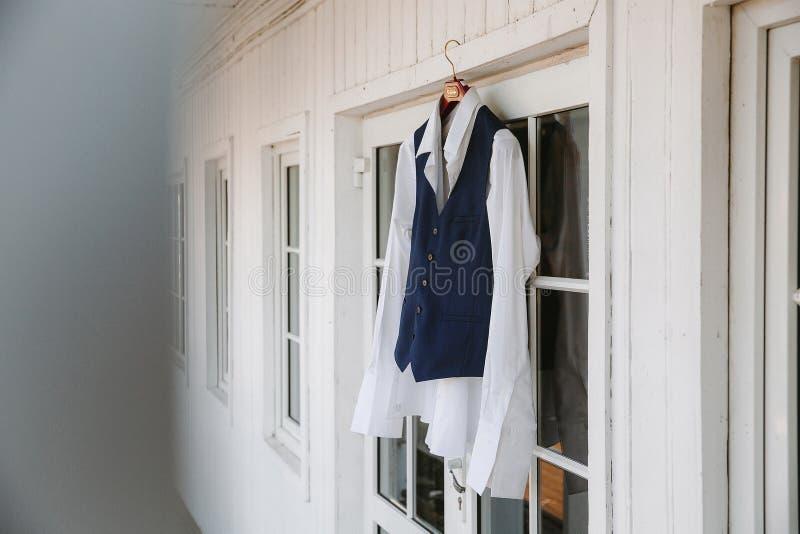 Il vestito dello sposo che appende su una parete bianca immagine stock