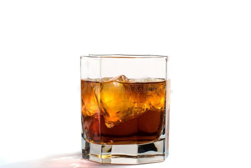 Il vetro caduto e di caduta del whiskey con ghiaccio e spruzza immagine stock