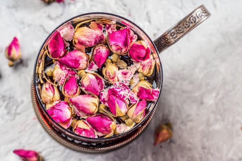 Il vetro d'annata della tazza di tè con i petali germoglia la rosa asciutta di rosa dei fiori fotografia stock