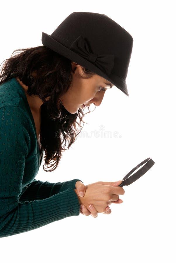 Il vetro del magnifier della giovane donna cerca qualcosa immagini stock