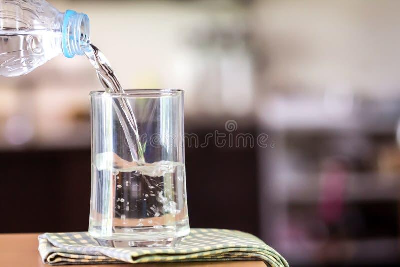 Il vetro dell'acqua purificata sulla barra della tavola nel kitchenroom fotografia stock