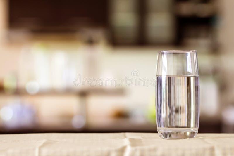 il vetro di acqua purificata sulla barra della tavola nel kitchenroom immagine stock