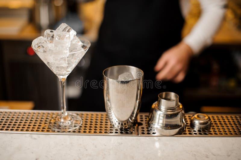 Il vetro di cocktail e dell'agitatore ha riempito di cubetti di ghiaccio sul contatore della barra immagini stock libere da diritti