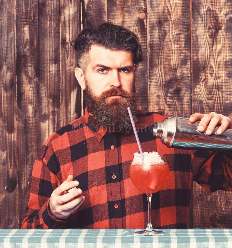 Il vetro di versamento dei pantaloni a vita bassa o del barista, fa la bevanda fresca con ghiaccio fotografie stock