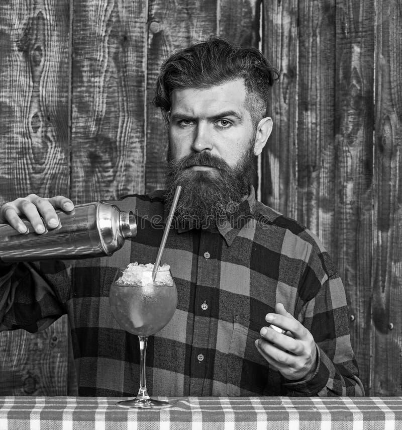 Il vetro di versamento dei pantaloni a vita bassa o del barista, fa la bevanda fresca con ghiaccio fotografia stock