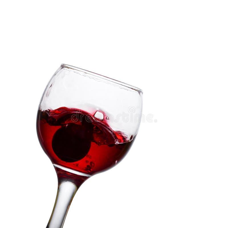 Il vetro di vino rosso ha inclinato su un fondo bianco immagine stock