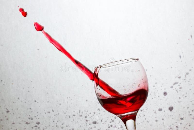 Il vetro inclinato di vino rosso ha perforato una corrente della bevanda alcolica immagini stock
