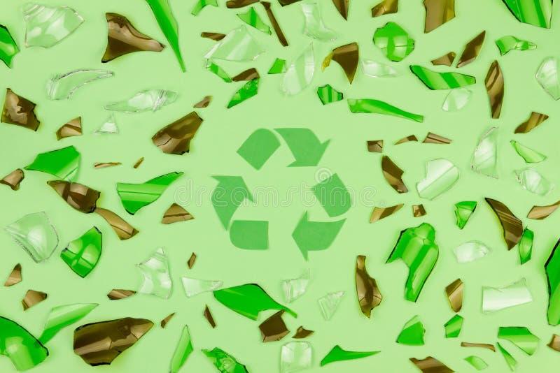 Il vetro incrinato su fondo verde con verde ricicla il simbolo fotografia stock