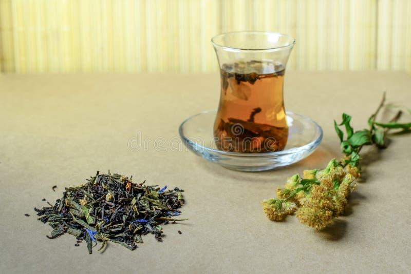 Il vetro tradizionale turco con tè su una tavola, vicino un piccolo gruppo del tè asciutto riempito e un'erba fotografie stock