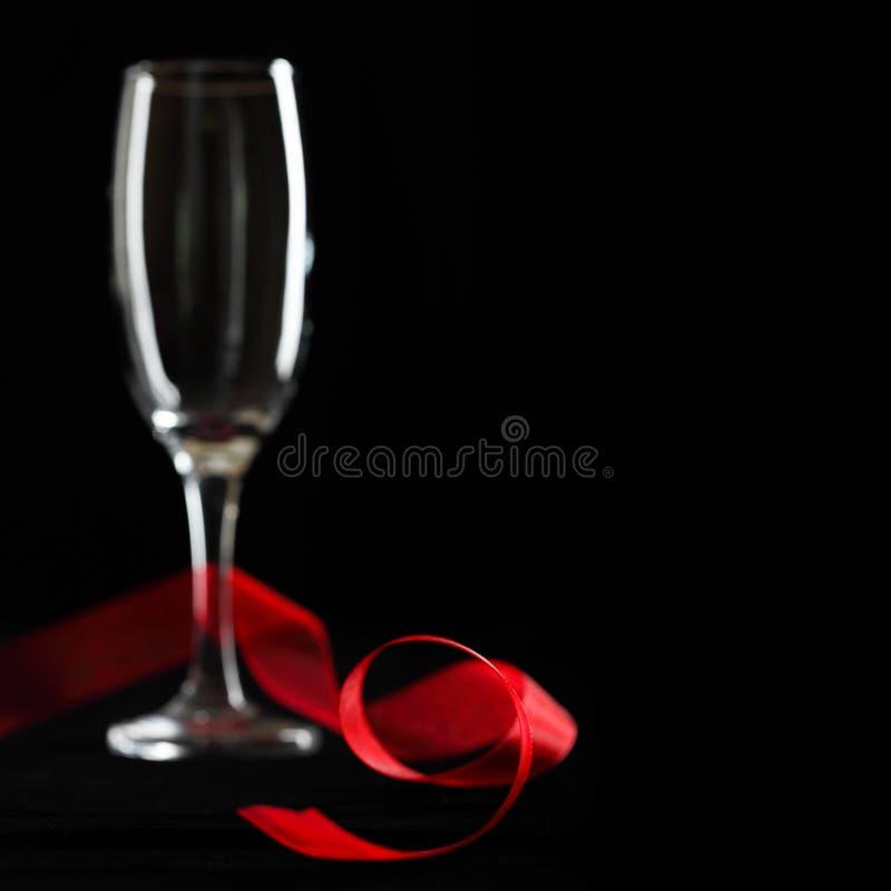 Vetro vuoto del champagne e nastro rosso. fotografia stock