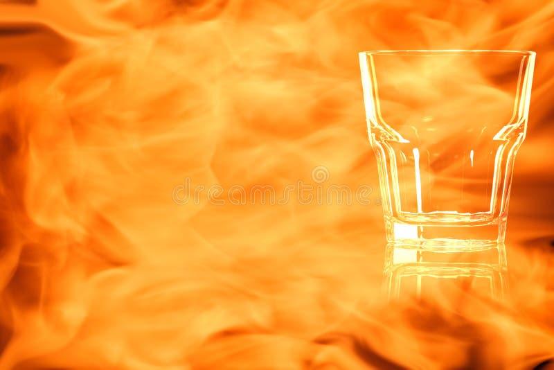 Il vetro vuoto per whiskey nel fuoco fiammeggia fotografia stock