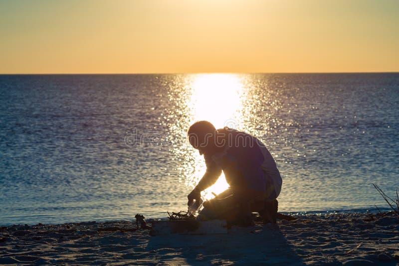 Il viaggiatore accende un falò sulla spiaggia durante il tramonto fotografie stock