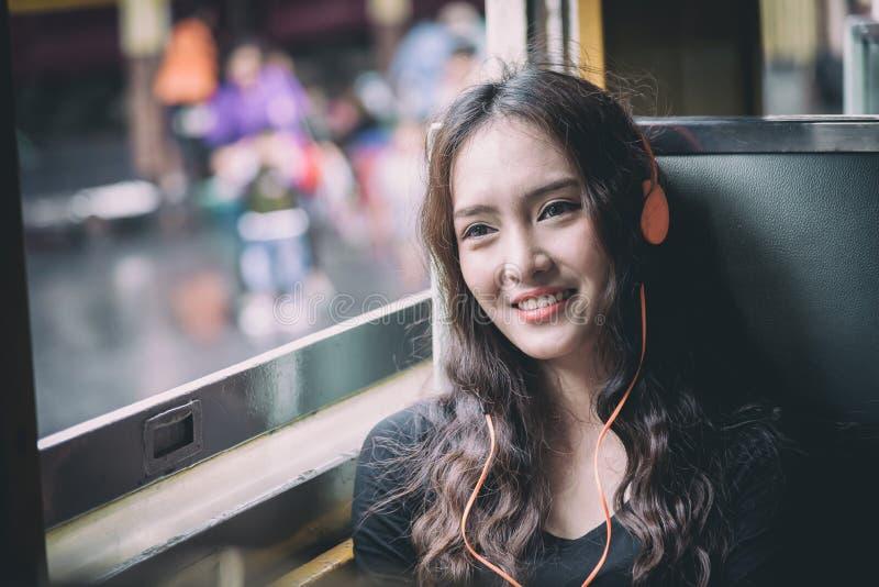 Il viaggiatore asiatico della donna ha musica d'ascolto con il telefono e la h arancio fotografia stock