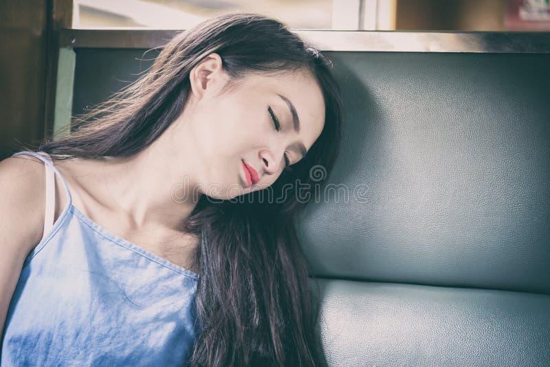 Il viaggiatore asiatico della donna ha sonno nel treno con felicità a fotografia stock