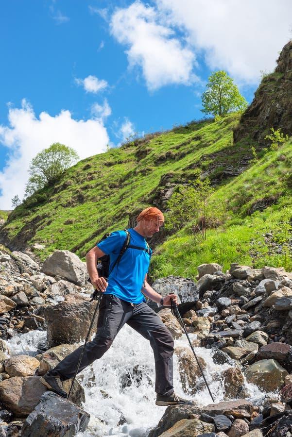 Il viaggiatore barbuto dell'uomo con lo zaino attraversa un fiume della montagna immagine stock