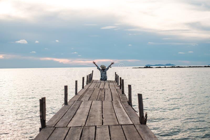 Il viaggiatore che la giovane donna dentro si siede da solo sul ponte di legno ha tramonto e fotografia stock libera da diritti