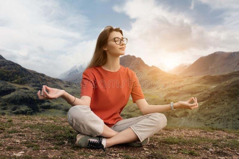 Il viaggiatore che si siede nelle montagne sta meditando nella posizione di loto Circondato dalla bella natura un il giorno soleg fotografia stock