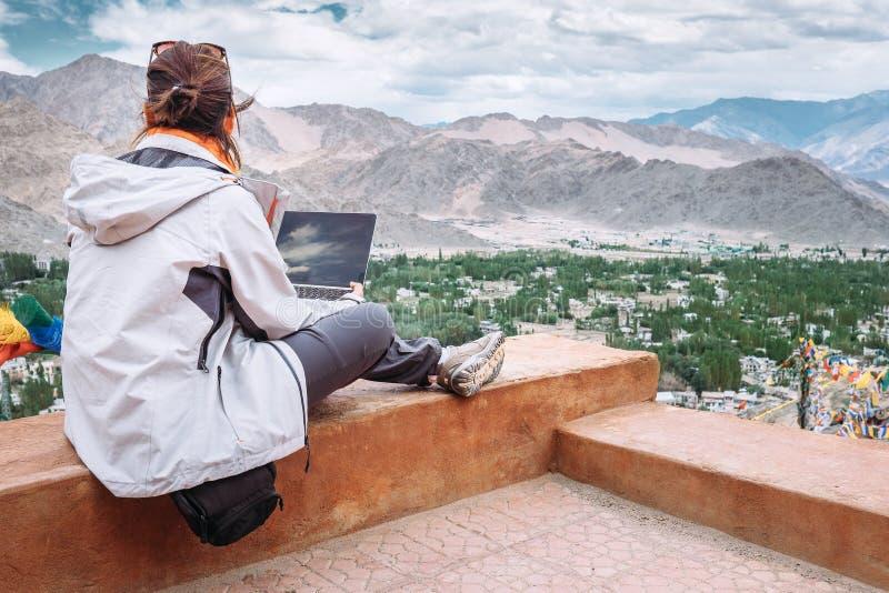 Il viaggiatore con il computer portatile si siede sul punto di vista superiore sul vall della montagna immagini stock