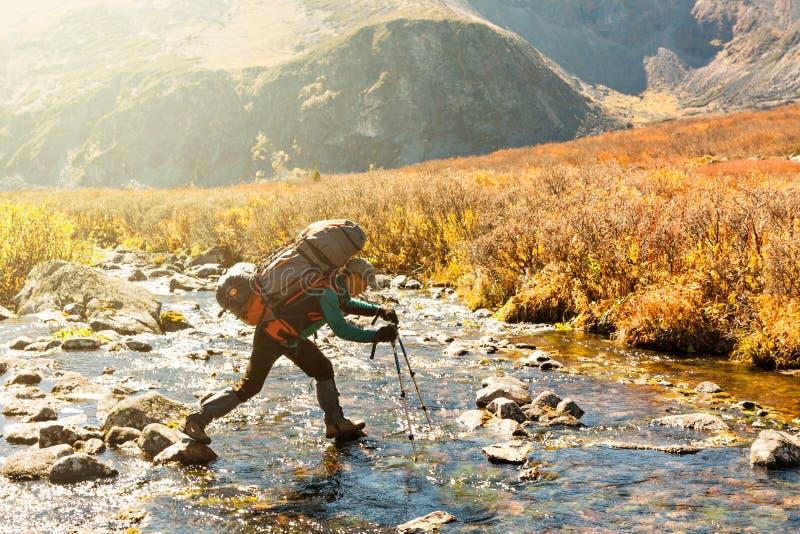 Il viaggiatore con zaino e sacco a pelo attraversa il fiume immagine stock libera da diritti