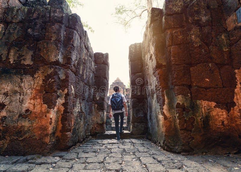 Il viaggiatore con zaino e sacco a pelo dell'uomo che cammina dentro in Prasat Muang Sing ? rovine antiche del tempio khmer fotografie stock libere da diritti