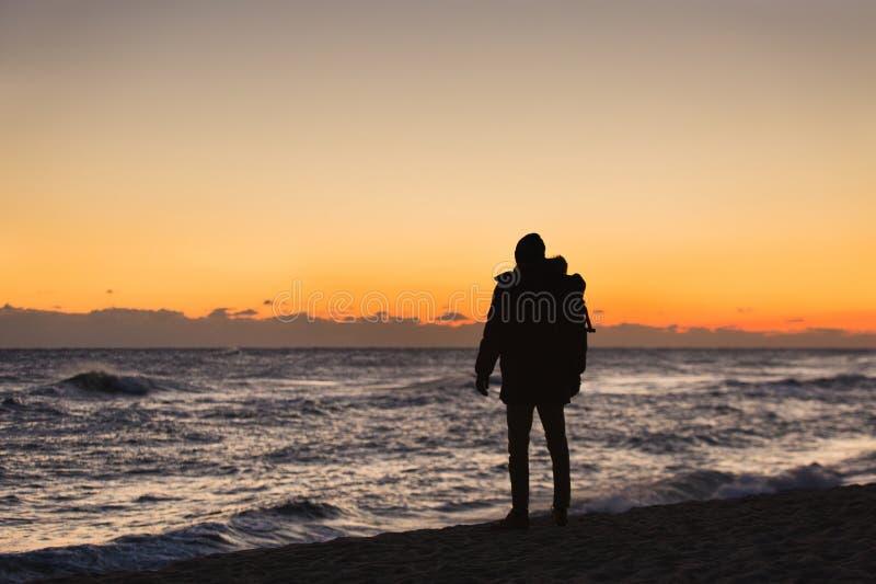 Il viaggiatore dell'uomo con uno zaino sta stando sulla spiaggia immagini stock libere da diritti