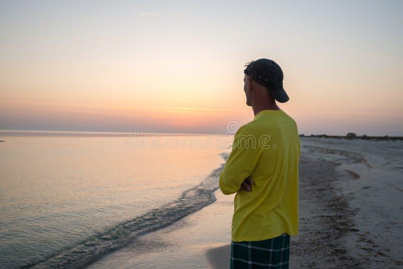 Il viaggiatore dell'uomo sta stando da solo in una linea della spuma e in un sunse pieno d'ammirazione fotografie stock libere da diritti
