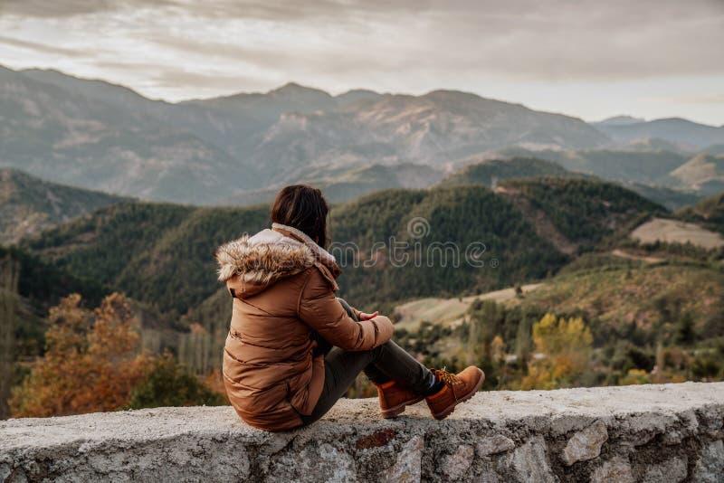 Il viaggiatore della donna esamina il bordo della scogliera delle montagne nei precedenti fotografie stock