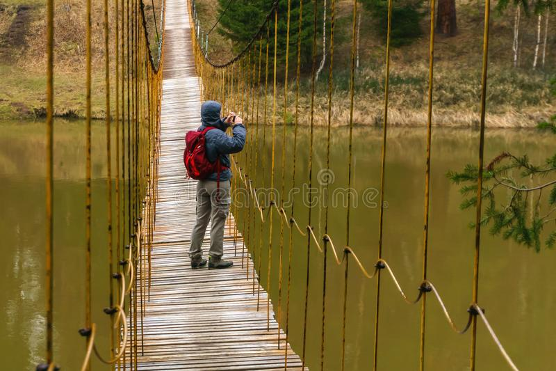 Il viaggiatore della donna prende un'immagine da un ponte sospeso sopra il fiume della molla fotografia stock libera da diritti