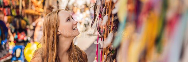 Il viaggiatore della donna sceglie i ricordi nel mercato a Ubud INSEGNA in Bali, Indonesia, formato lungo fotografia stock libera da diritti