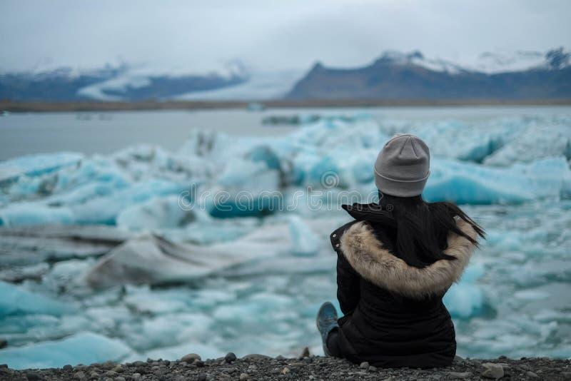 Il viaggiatore delle donne si siede sulla terra e sull'esame del jokulsarlon della laguna del ghiacciaio fotografia stock