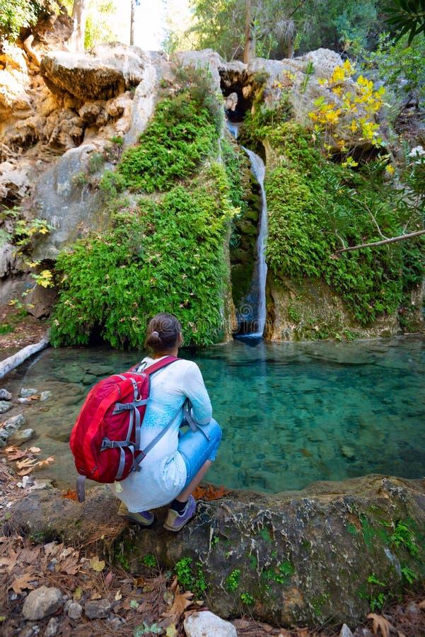 Il viaggiatore, donna ammira la cascata che scorre lungo la scogliera immagini stock libere da diritti