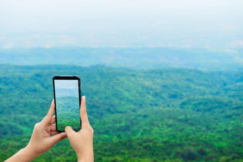 Il viaggiatore fa la foto sullo smartphone, facendo uso del telefono a disposizione, blogger di viaggio, fine su di women& x27; m fotografia stock