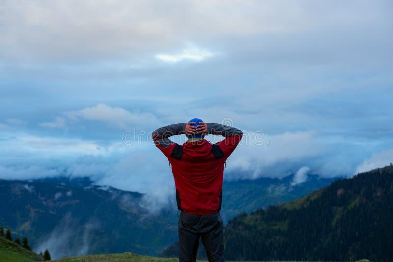 Il viaggiatore felice ammira l'enorme si rannuvola la valle della montagna immagini stock