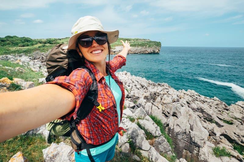 Il viaggiatore felice di viaggiatore con zaino e sacco a pelo della donna prende una foto del selfie sullo stupore della o fotografia stock libera da diritti