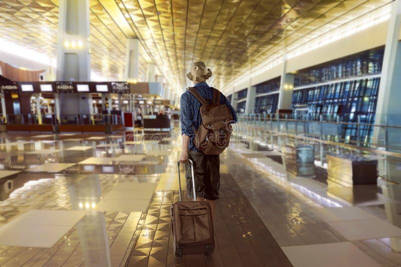 Il viaggiatore porta la sua borsa nell'aeroporto fotografie stock