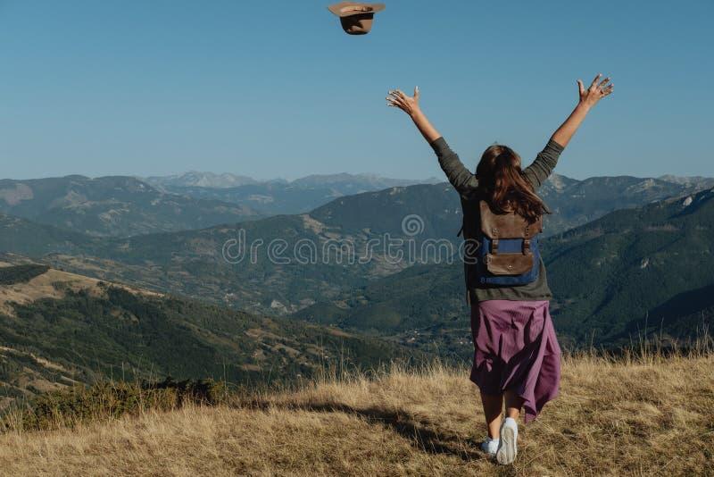 Il viaggiatore posteriore della donna lancia un cappello contro lo sfondo della m. fotografia stock libera da diritti