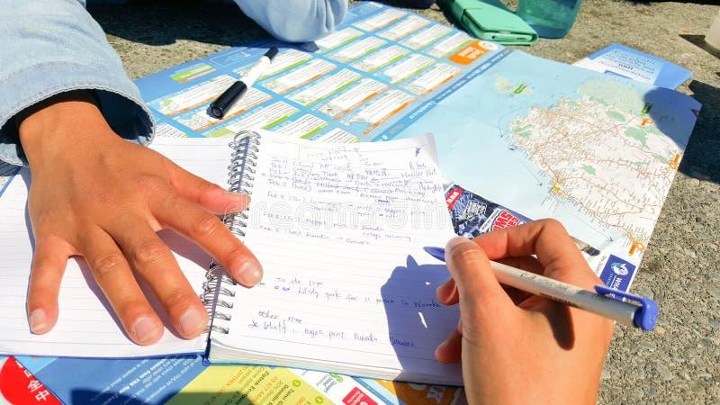 Il viaggiatore scrive le note su un taccuino circa il programma di corsa fotografia stock