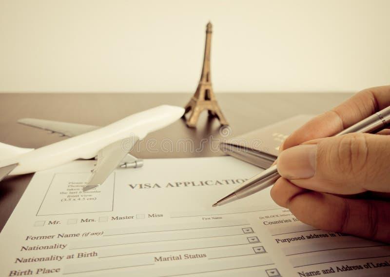 Il viaggiatore sta riempiendo la forma di visto per viaggiare a Parigi fotografie stock