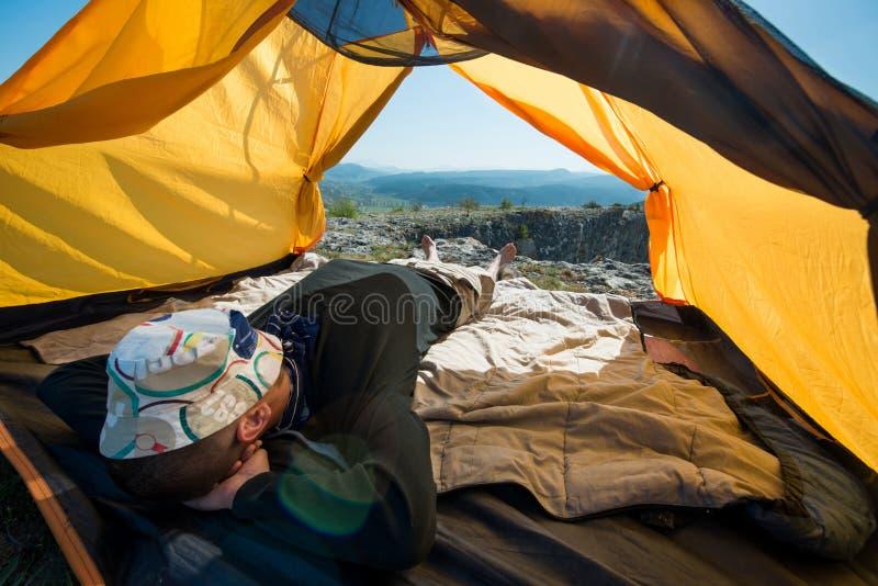 Il viaggiatore sta riposando dentro una tenda all'aperto immagine stock