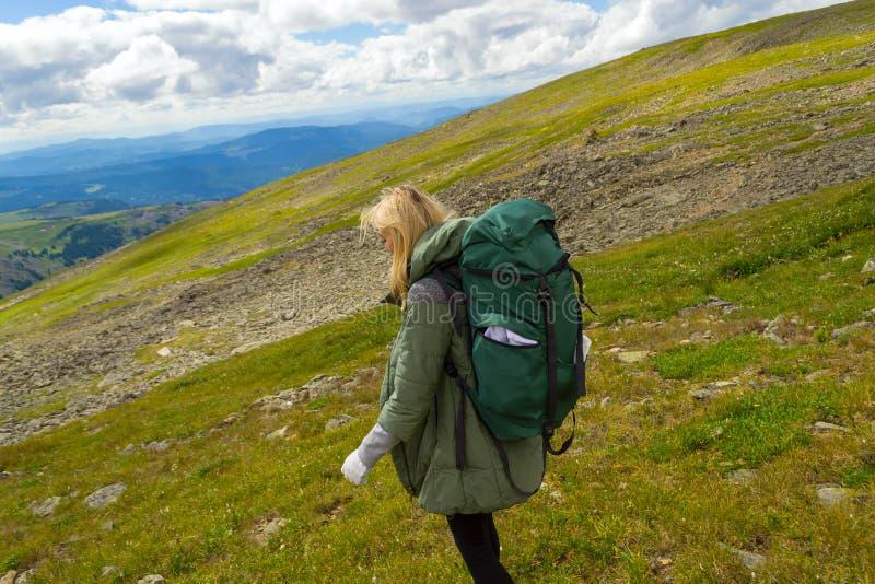 Il viaggio della ragazza con il grande zaino verde scende la collina sulle rocce verso i campi verdi in montagne di altai nominat fotografie stock libere da diritti