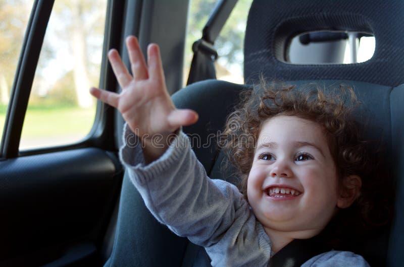 Il viaggio felice del piccolo bambino in un'automobile si siede fotografia stock