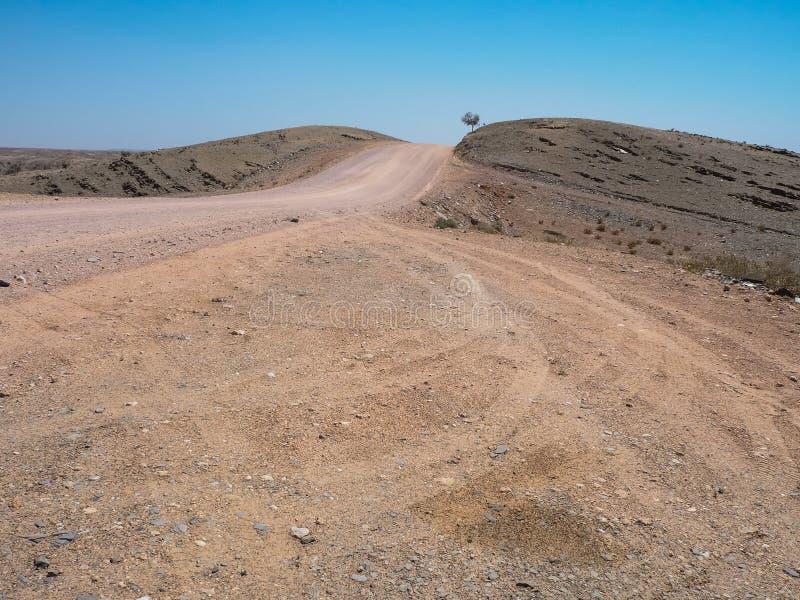 Il viaggio stradale tramite la strada non pavimentata polverosa ruvida con la pista del pneumatico dell'automobile con il clima d fotografia stock libera da diritti