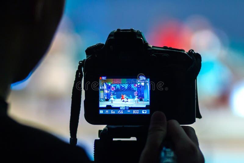 Il videographer registra un certo genere di prestazione astratta del ` s del nuovo anno degli artisti in scena con l'aiuto della  fotografia stock libera da diritti